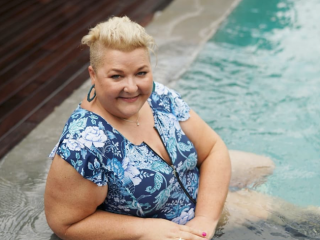 Jenni from Styling Curvy is sitting in the pool in her Crane Birds Frill Sleeve one pieces from Curvy Swimwear.