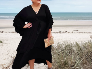A lady standing on a beach wearing a black dress and pewter shoes.